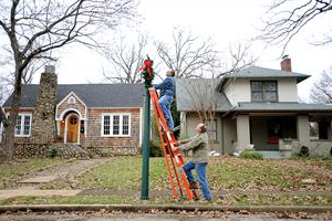 Staff Photo by Allison Kwesell Scott Harrison, top, and Ray Gross hang a wreath on a lightpole on Eveningside Drive at Ferger Place. Ferger Place is having a Christmas Tour of Homes in preperation for it's 100th anniversary next year.